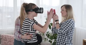 Girls playing game with virtual reality goggles and mobile phone at home stock video