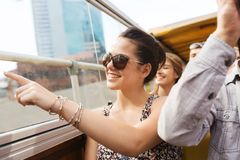Teenage girl with friends traveling by tour bus. Travel, tourism, summer vacation, sightseeing and people concept - happy teenage girl in sunglasses with group Royalty Free Stock Images