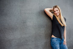 Teenage girl in front of concrete wall Stock Image