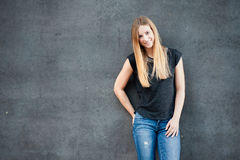 Teenage girl in front of concrete wall Stock Photo