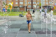 Teenage girl fun running between the fountains in the Park stock photos