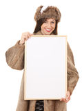 Teenage girl in fur clothes with blank board Royalty Free Stock Photos