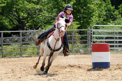 Teenage girl galloping around a turn in a barrel race Stock Photography