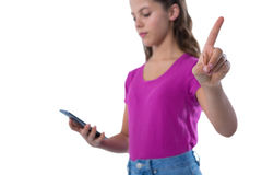 Teenage girl gesturing while using mobile phone. Against white background Royalty Free Stock Photo