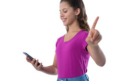 Teenage girl gesturing while using mobile phone. Against white background Stock Photography