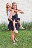Teenage girl giving sister a piggyback ride Royalty Free Stock Image