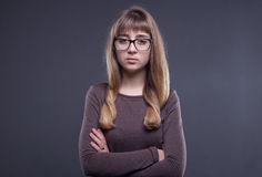 Teenage girl in glasses with arms crossed. On gray background stock images