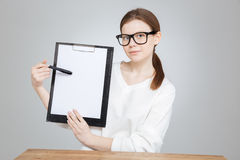 Teenage girl in glasses showing and pointing on blank clipboard Royalty Free Stock Photo