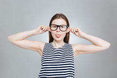 Teenage girl in glasses showing tongue and making funny face Royalty Free Stock Photography