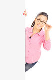 Teenage girl with glasses standing behind blank panel Stock Photo