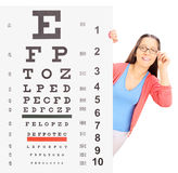 Teenage girl with glasses standing behind eyesight test Stock Image