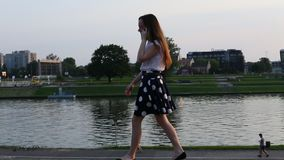 Teenage girl goes on a city promenade and talking on cell phone. stock video footage