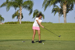 Teenage girl golfing. Teenage girl ready to drive a golf ball on a golf course in Naples, Florida Royalty Free Stock Images