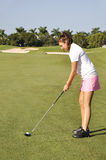 Teenage girl golfing royalty free stock image