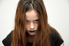 Teenage girl in gothic style looking very angry. Very angry teenage girl with tangled hair and mad look stock image