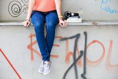Teenage girl and graffiti. Teenage girl sitting in front of graffiti Stock Photography