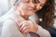 A teenage girl with grandmother at home, hugging. royalty free stock images