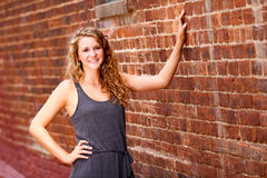 Teenage Girl Gray Dress Brick Wall. A beautiful blond teenage girl next door with curly hair and a pretty smile in a gray dress in front of a red brick wall in Stock Photography