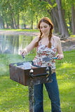 Teenage Girl Grilling Hamburgers at a Park. Teenage girl cooks hamburger patties on a barbecue grill at a park. Vertical format Royalty Free Stock Images