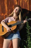 Teenage girl with guitar. Against old rusty wall background near the nettle bush Stock Image