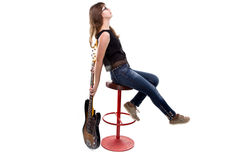 Teenage girl with guitar sitting on bar stool. On white background Royalty Free Stock Photography