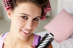 Teenage girl with hair in curlers Royalty Free Stock Images