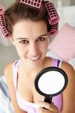 Teenage girl with hair in pink curlers Royalty Free Stock Photography