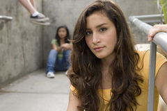 Teenage girl (13-15) with hand on railing, friends in background, portrait Stock Photography
