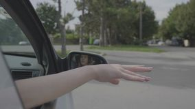 Teenage girl hand waving her arm outside the window car during the summer trip -. Teenage girl hand waving her arm outside the window car during the summer trip stock footage