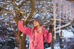 Teenage Girl Hanging Fairy Lights In Tree With Ici Royalty Free Stock Image
