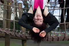 Teenage Girl Hanging Upside Down on Jungle Gym Stock Photo