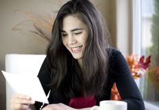 Teenage girl happily reading note in hand. Teenage girl or young woman happily reading note in hand, smiling stock photos