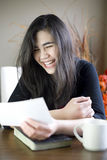 Teenage girl happily reading note in hand Stock Images