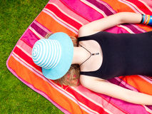 Teenage Girl with a hat covering her face lying on her back Royalty Free Stock Images