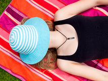 Teenage Girl with a hat covering her face lying on her back Stock Image