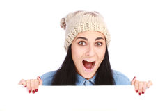 Teenage girl with a hat hiding behind a billboard. Young attractive emotional teenage girl with a hat hiding behind a billboard and looking up isolated on white Stock Photography