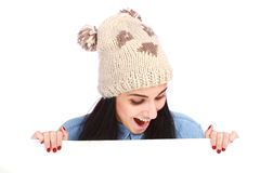 Teenage girl with a hat hiding behind a billboard. Young attractive emotional teenage girl with a hat hiding behind a billboard and looking down isolated on Stock Images