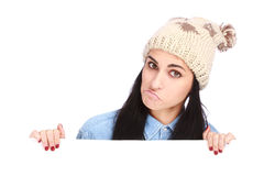 Teenage girl with a hat hiding behind a billboard royalty free stock images