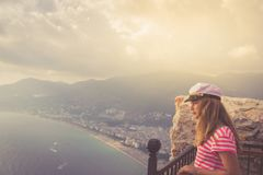A teenage girl in a hat looking out into the distance against the background of the mountains and sea.  stock photos