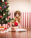 A teenage girl in a hat sitting near the Christmas tree Stock Photos