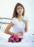 Teenage girl having belly pain and taking pills Stock Image