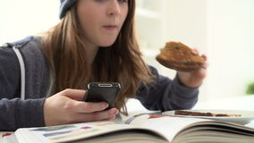 Teenage Girl Having Breakfast Whilst Sending Text Message. Teenage girl eating slice of toast whilst sending text message on mobile phone.Shot on Sony FS700 in stock footage