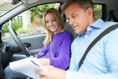Teenage Girl Having Driving Lesson With Instructor. Looking At Notes stock photography
