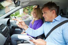 Teenage Girl Having Driving Lesson With Instructor. Pointing In Front Of Him Whilst Holding A Clipboard And Pen stock photography