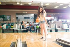 Teenage girl having fun in a bowling alley. Full length view of teenage girl having some fun in a bowling alley with her friends royalty free stock photos