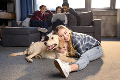 Teenage girl having fun with golden retriever dog while friends sitting on sofa. Smiling teenage girl having fun with golden retriever dog while friends sitting Stock Photography