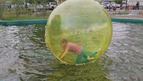 Teenage girl having fun running and turning inside zorb on water. Editorial. Omsk,Russia - May 20. 2017. Girl teenager in zorb bubble ball swimming in pool stock video