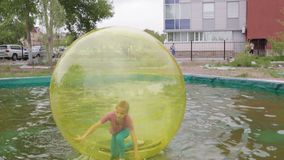 Teenage girl having fun running and turning inside zorb on water. Editorial. Omsk,Russia - May 20. 2017. Girl teenager in zorb bubble ball swimming in pool stock footage