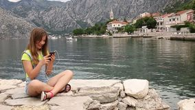 Girl having fun with smart phone on summer vacation