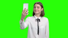 Teenage girl having online video chat using smartphone. Green screen hromakey background for keying stock video